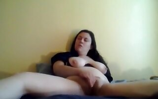 Chubby brunette gets naked and masturbates with a dildo on her bed